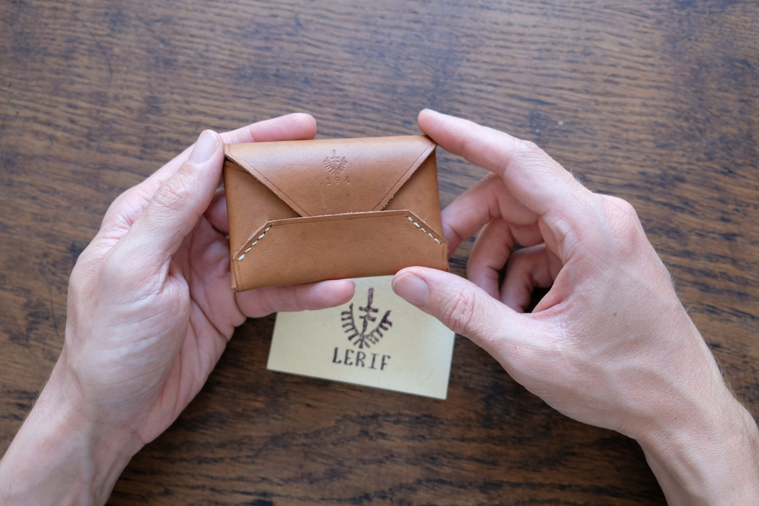 hands holding lerif designs leather airmail cardholder in walnut with wood and business card in background