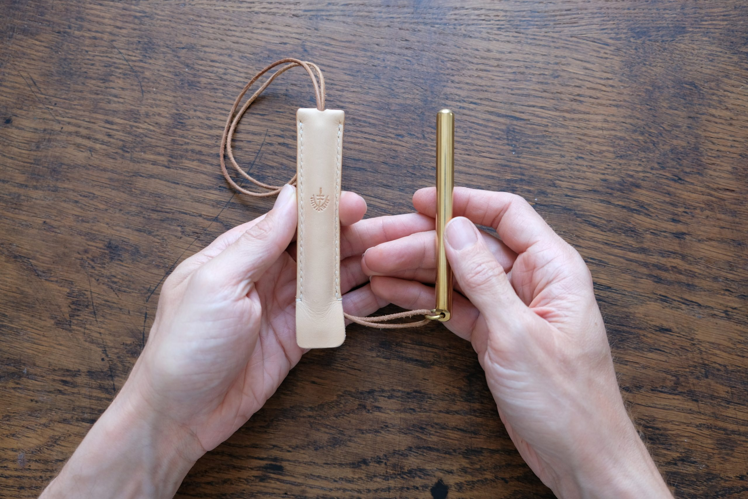 hands holding lerif designs brass pen and leather etuis