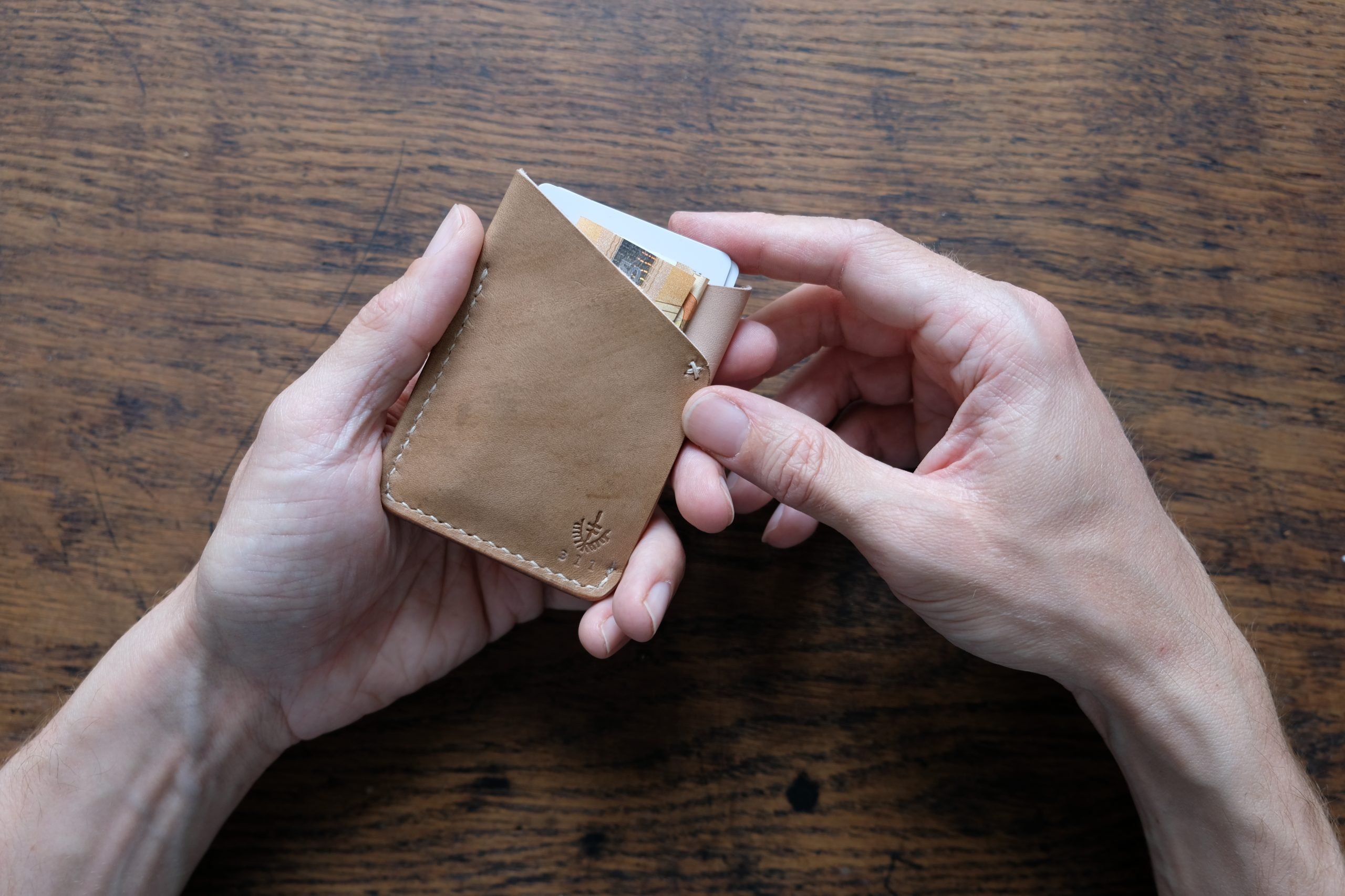 hands holding lerif designs leather fox ears cardholder in walnut and natural on wood background