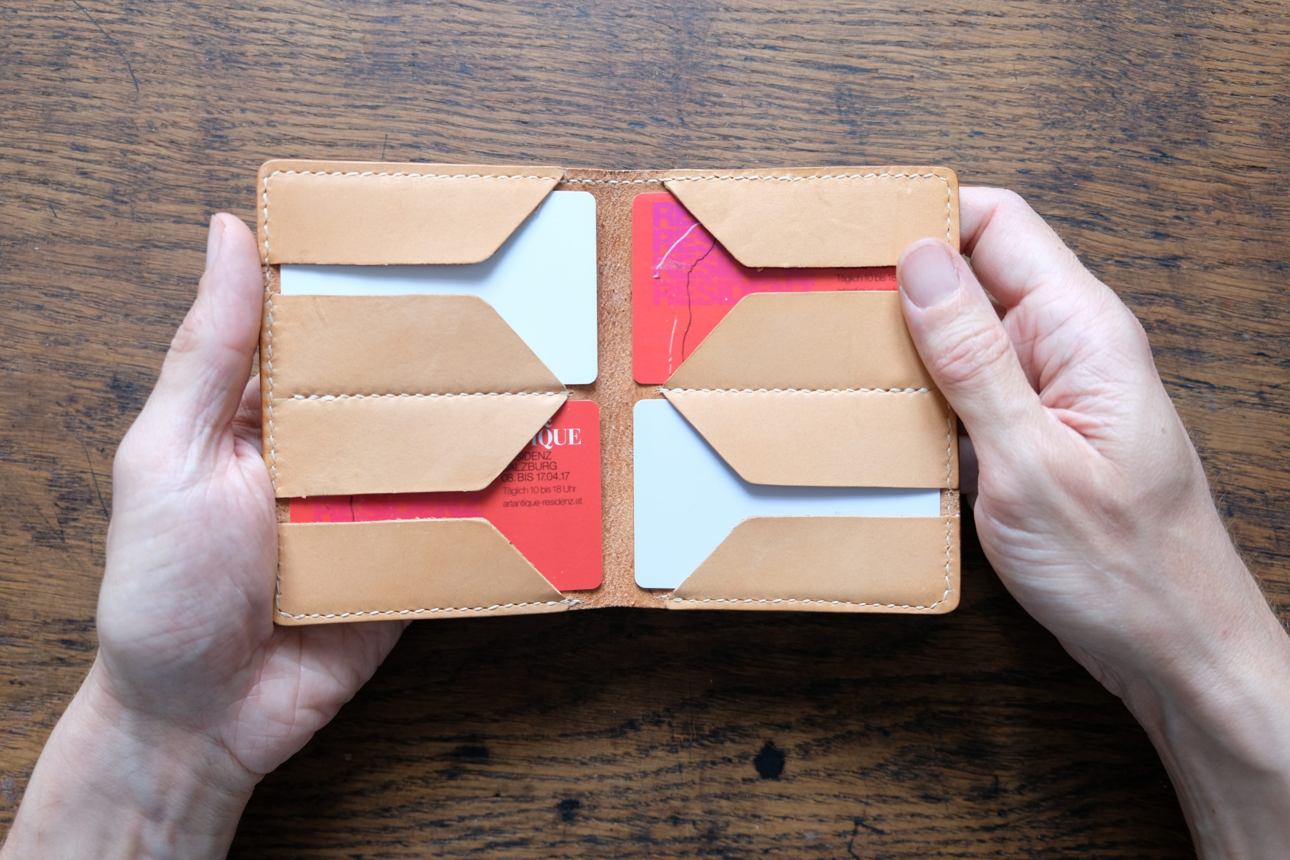 lerif designs large format leather bifold wallet held by hands on wood background demonstrating card pockets