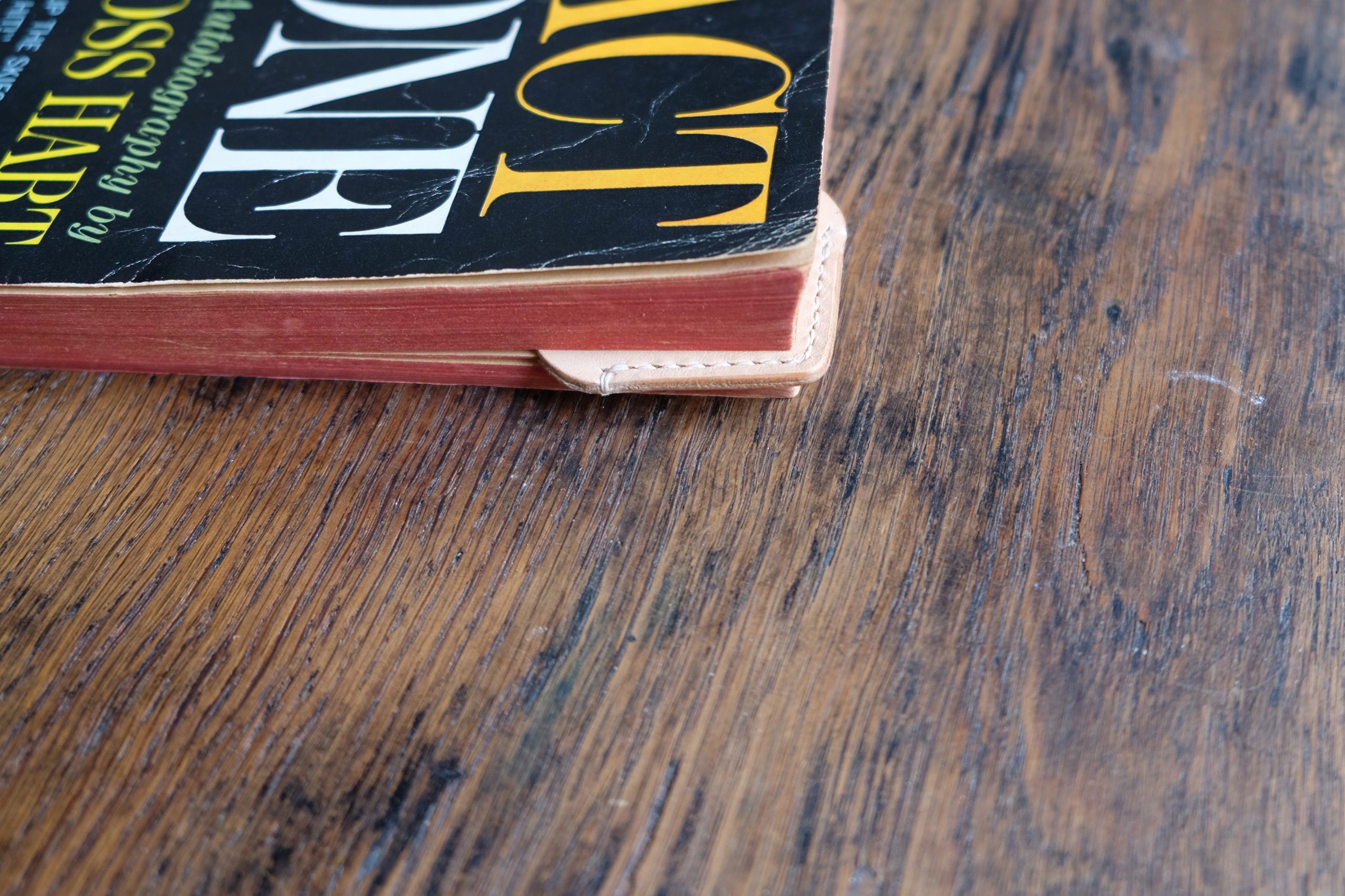 lerif designs love leather bookmark on corner of closed book on wood background