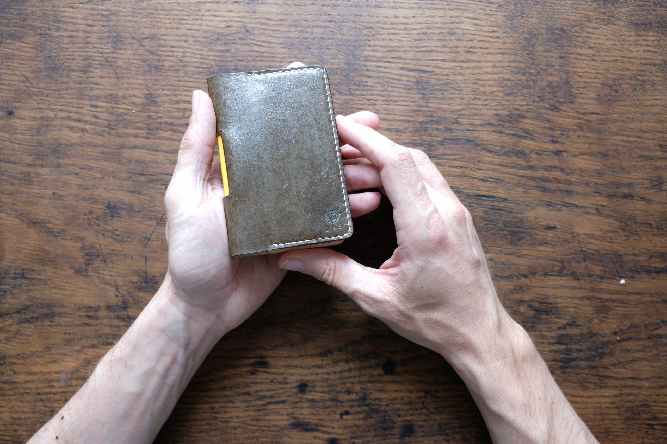 hands holding lerif designs leather notebook etuis on wood background
