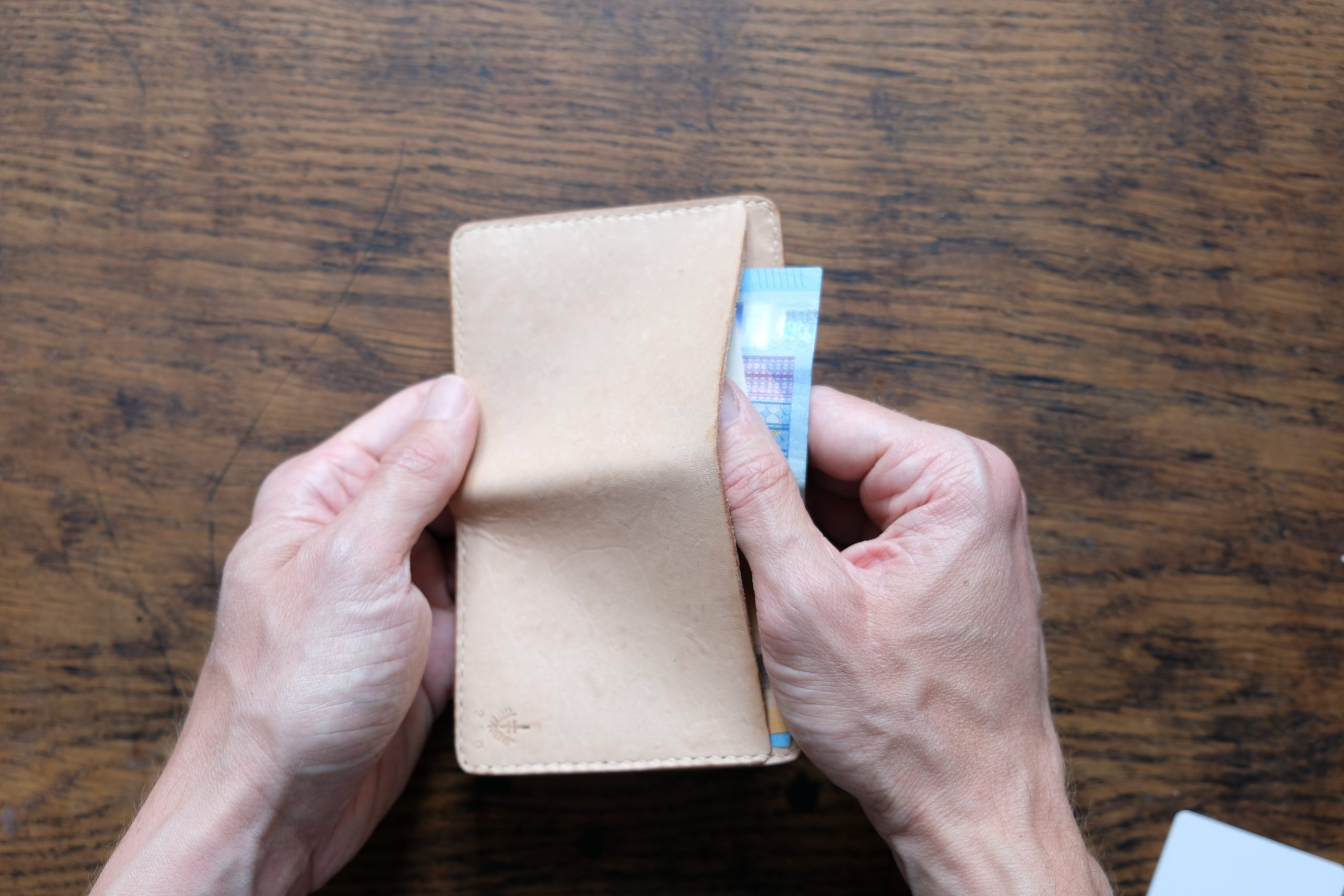 lerif designs small bifold leather wallet in natural on wood background pulling cash
