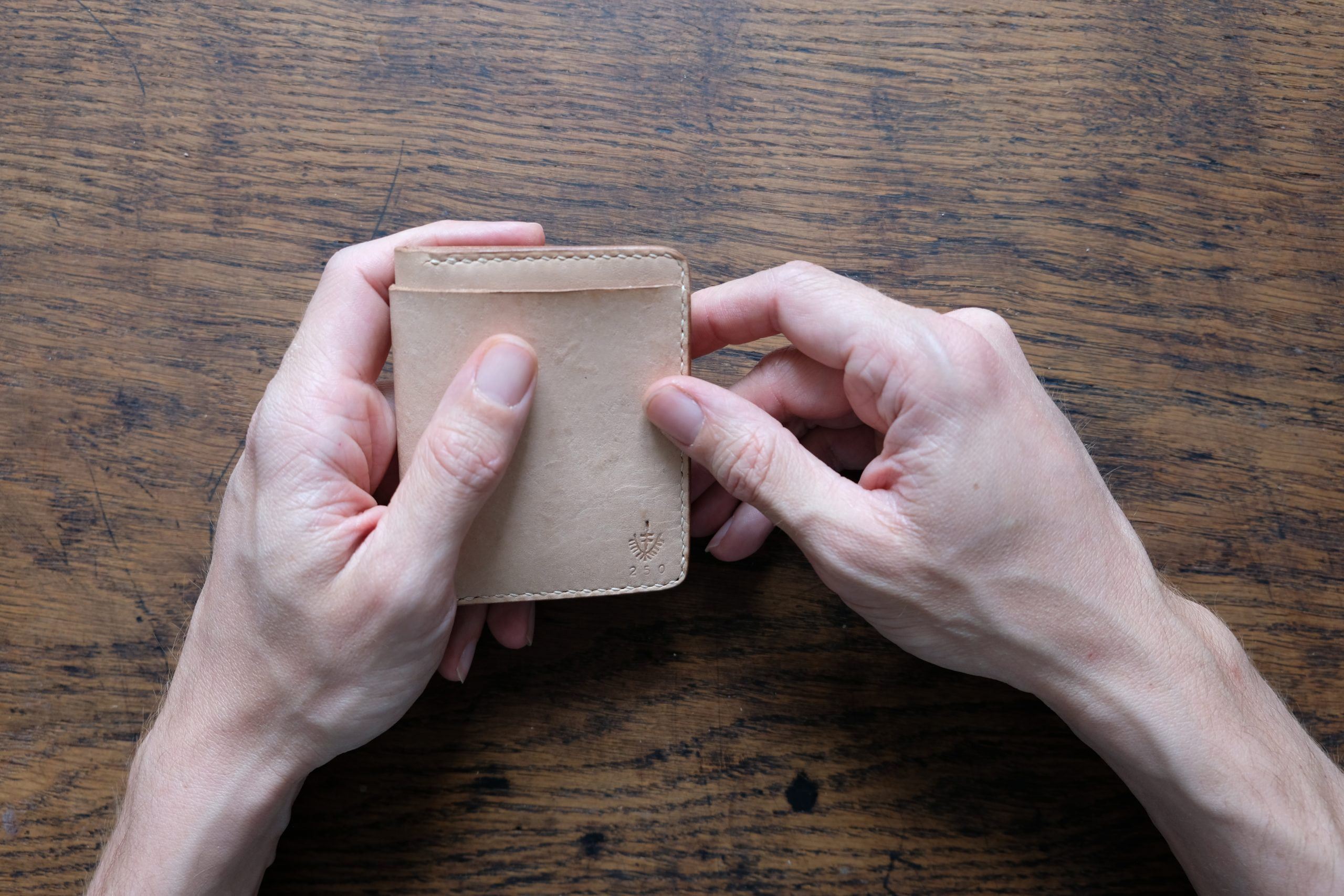 lerif designs small bifold leather wallet in natural on wood background held by hands