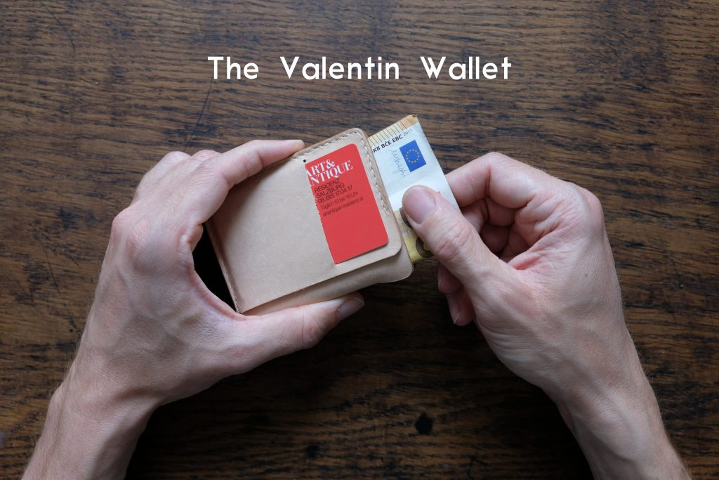 lerif designs hands pulling cash out of valentin wallet on wood background