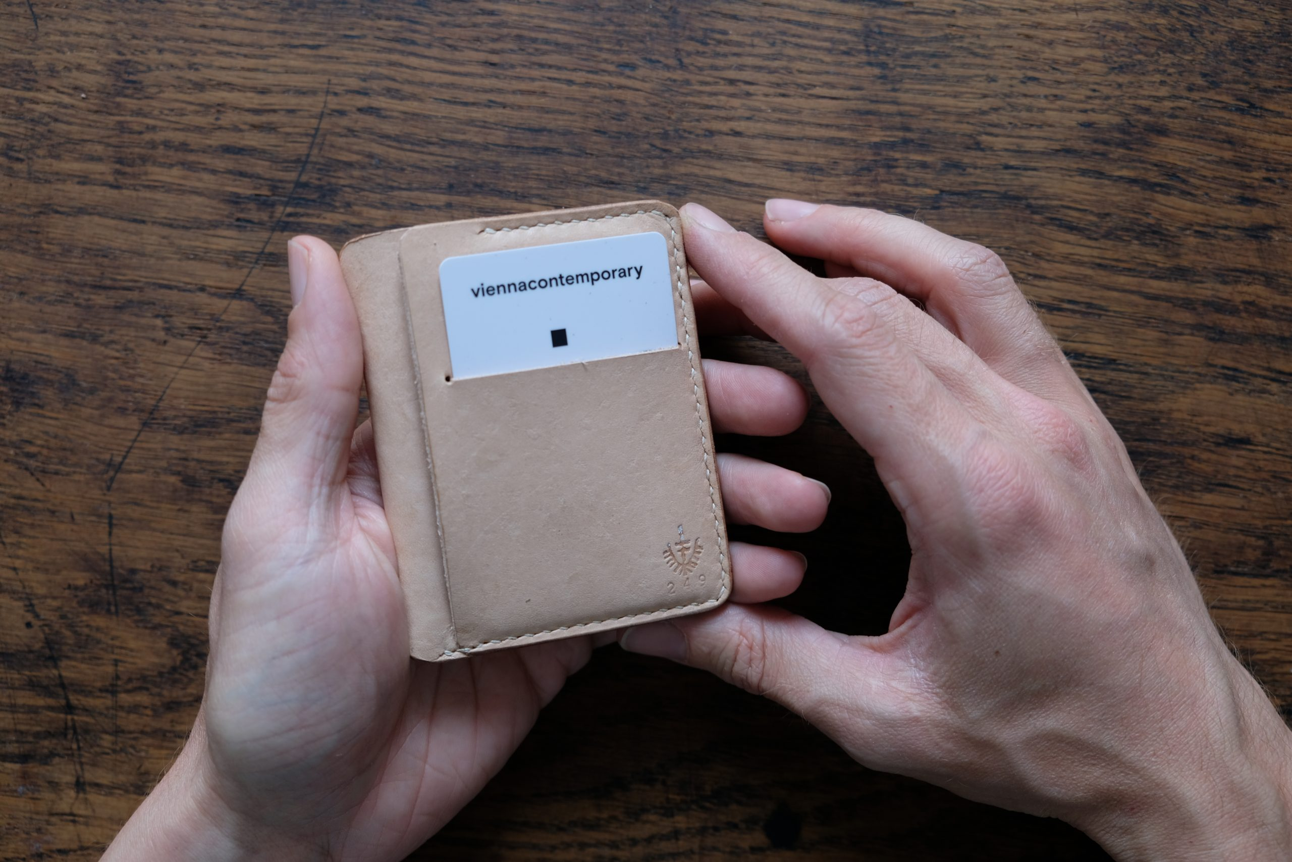 hands holding lerif designs valentin leather wallet in natural on wood background