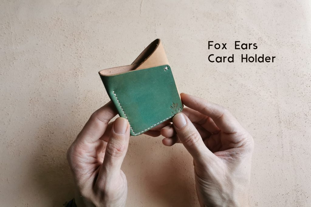 hands holding lerif designs fox ears card holder on beige background