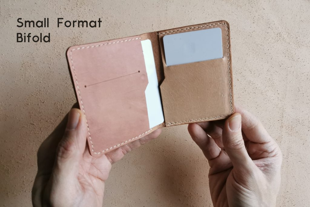 lerif designs hands holding small format bifold wallet with cards peeking out
