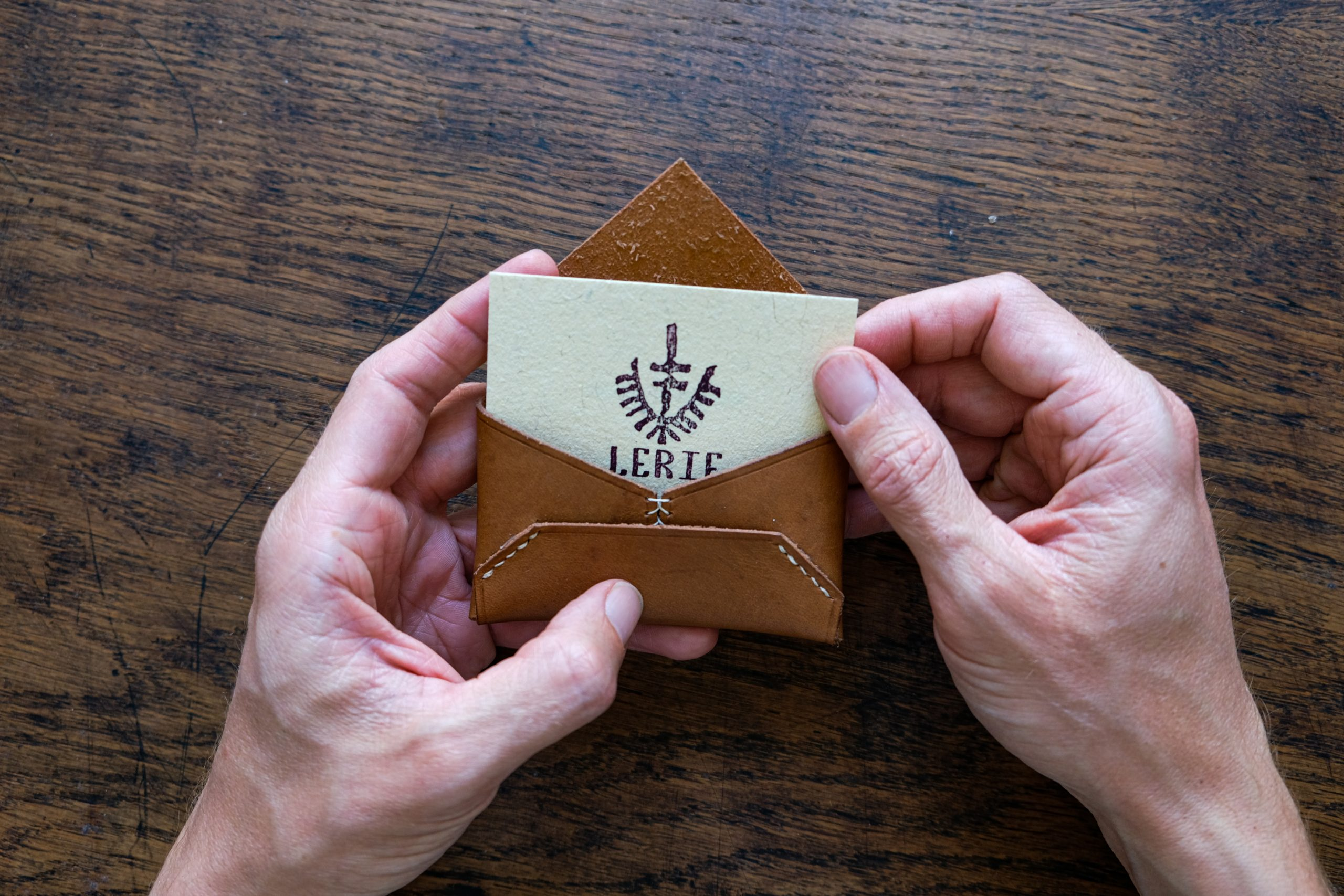 lerif designs leather airmail business card holder in walnut on wood background with brand business card inside