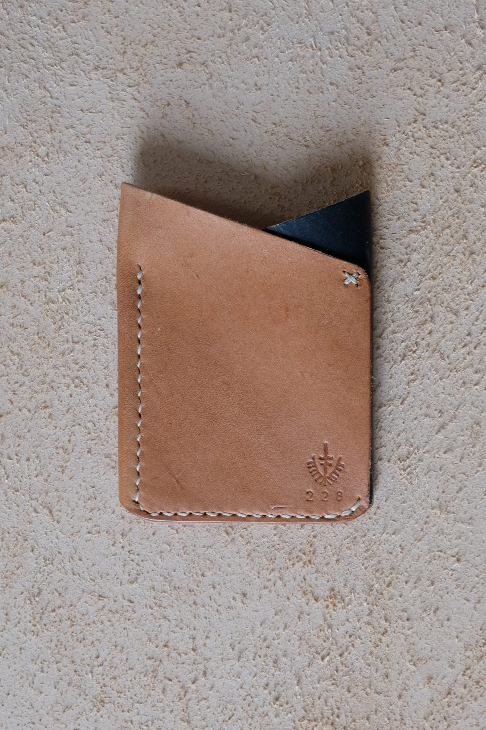 lerif designs leather fox ears cardholder in natural and indigo on beige backgroun