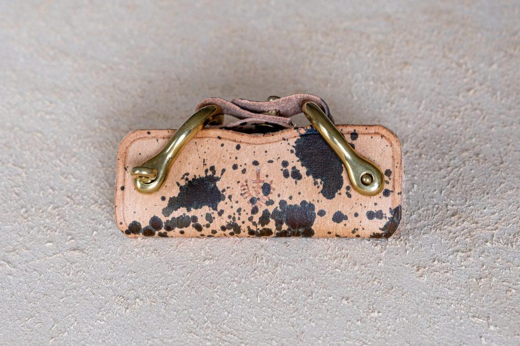 lerif designs leather horse buckle key holder splash vinegaroon on beige background