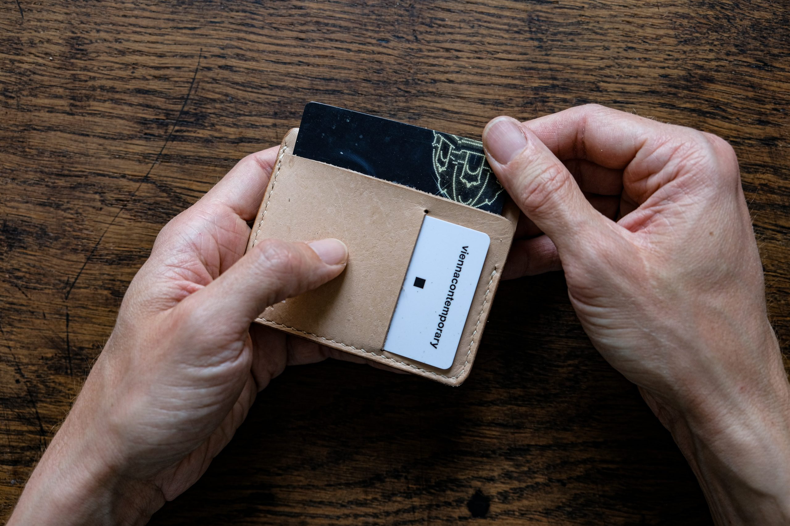 lerif designs Vale leather wallet in natural hands demo on wood background