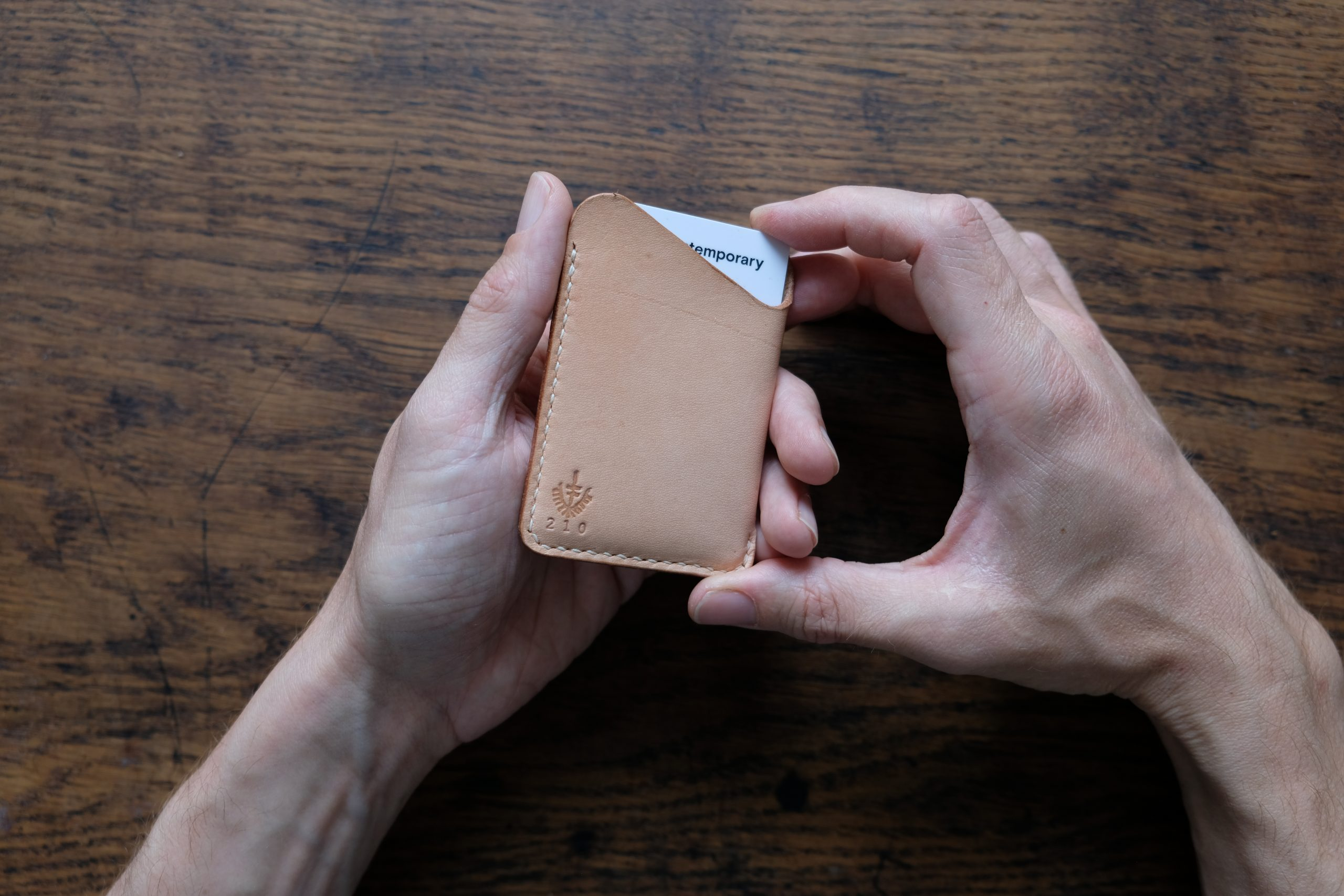 lerif designs leather wave cardholder demo with hands and card on wood background