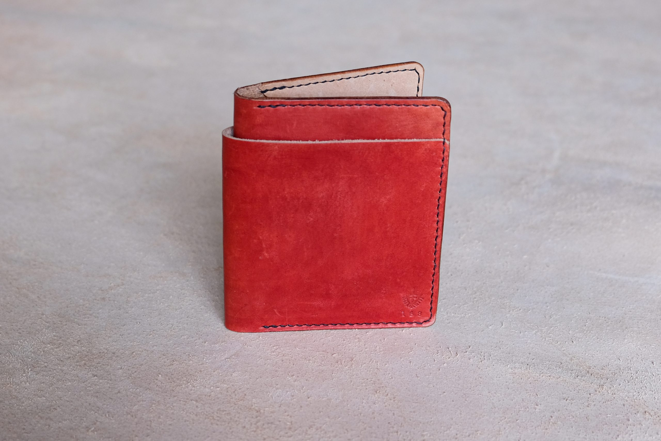 lerif designs large format leather bifold wallet in pomegranate and black stitching on beige background