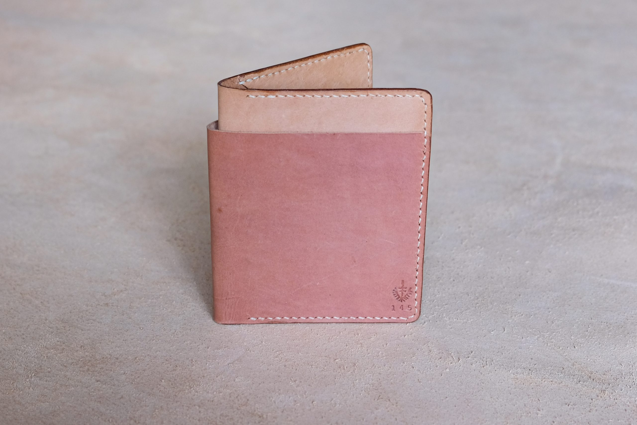 lerif designs large format leather bifold wallet in beet natural on beige background