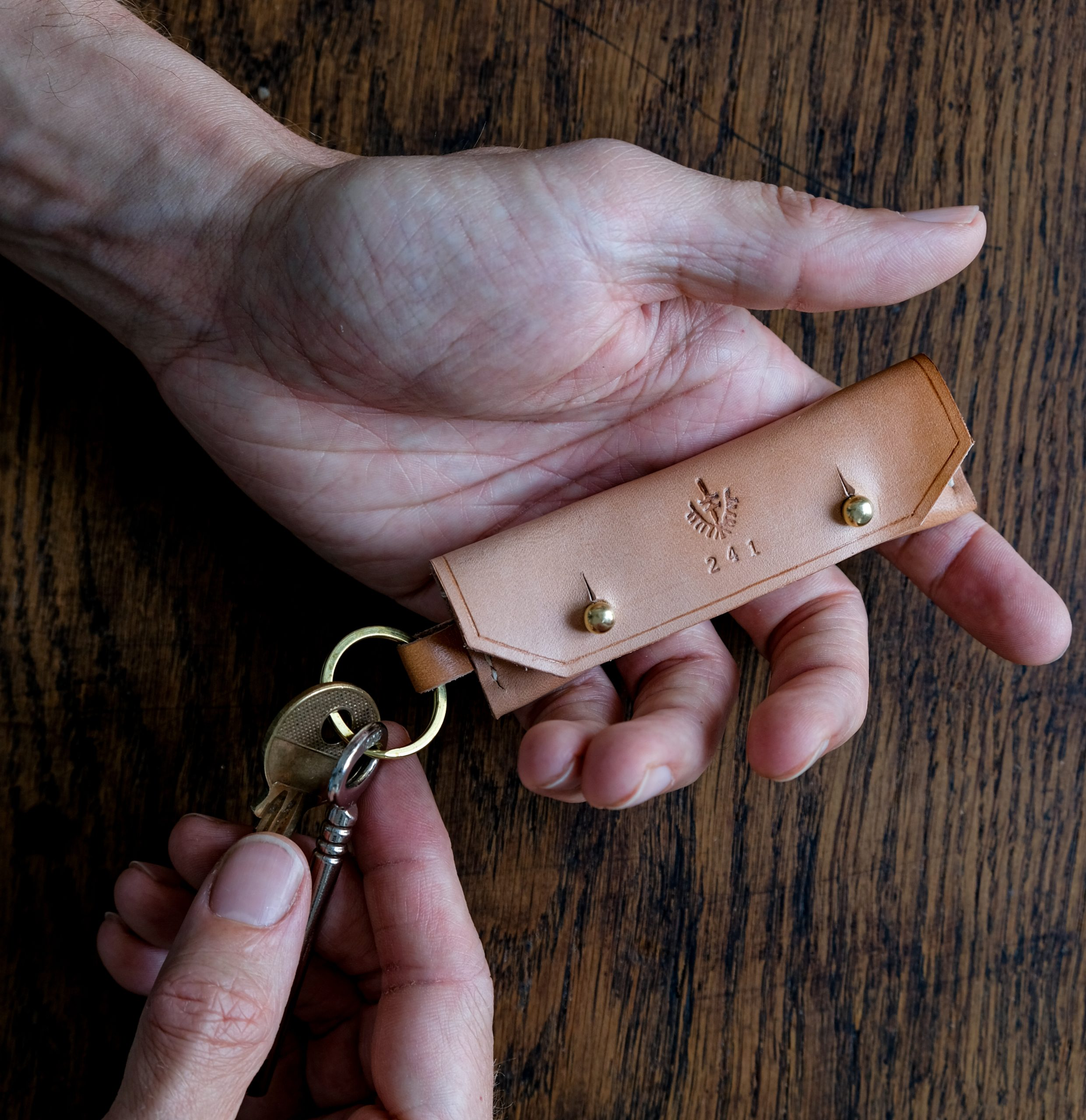 lerif designs leather gum stick coin holder demo with hands on wood background