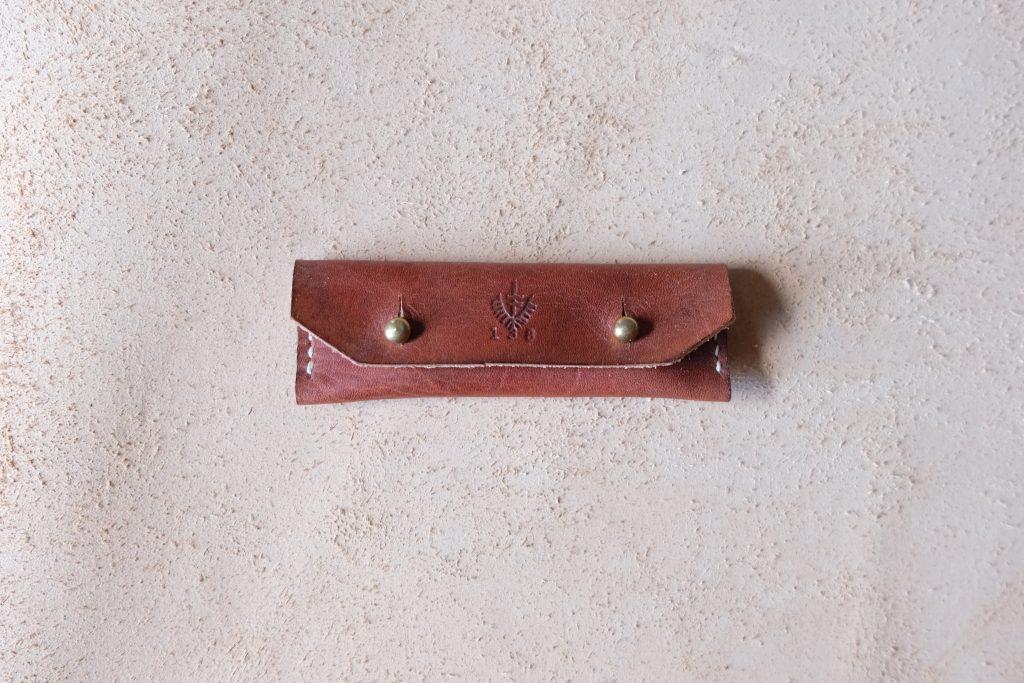 lerif designs leather gum stick coin holder on beige background burgundy with brass ring