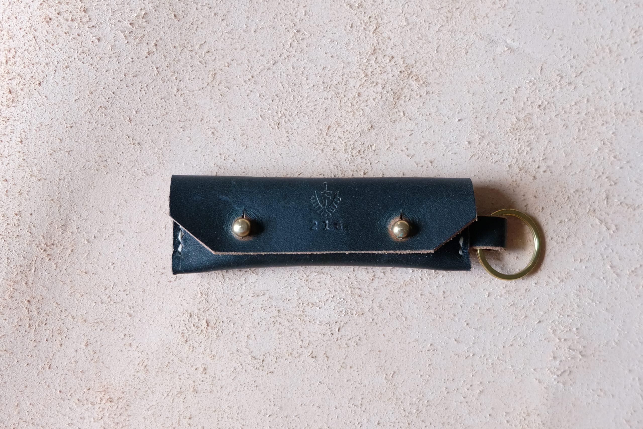 lerif designs leather gum stick coin holder on beige background indigo with brass ring