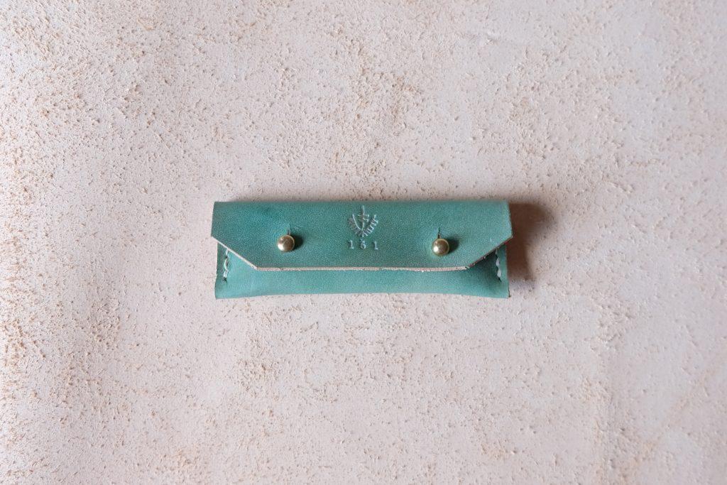 lerif designs leather gum stick coin holder on beige background pistachio