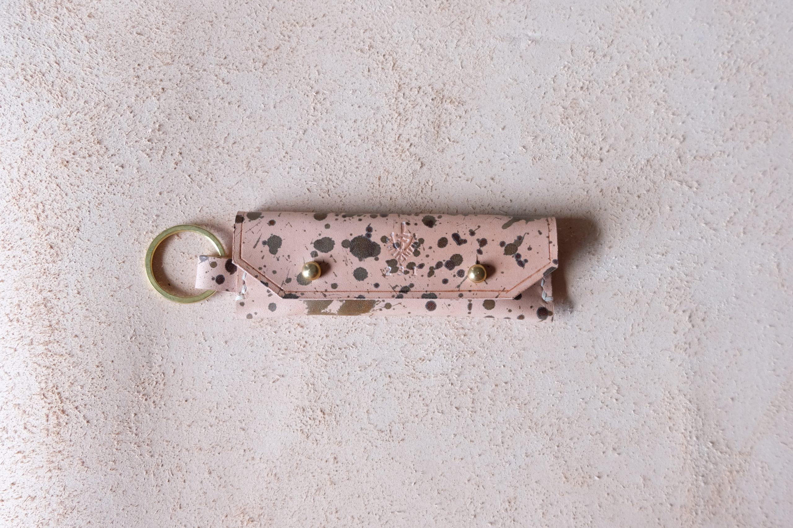 lerif designs leather gum stick coin holder on beige background variegata with brass ring