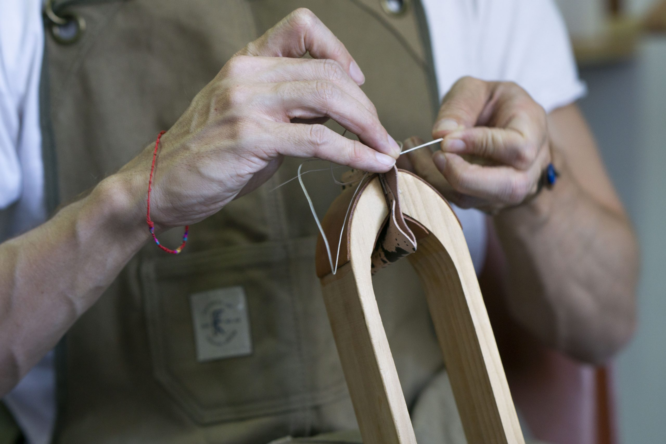 Lerif Designs Ayman's hands stitching a leather item in a stitching horse