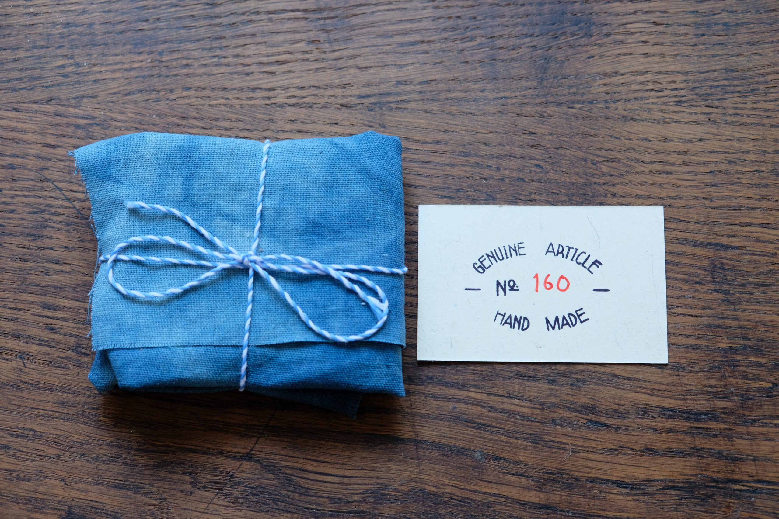 Lerif Designs leather goods wrapped in indigo cloth with card 'genuine article No. 160 Hand Made'