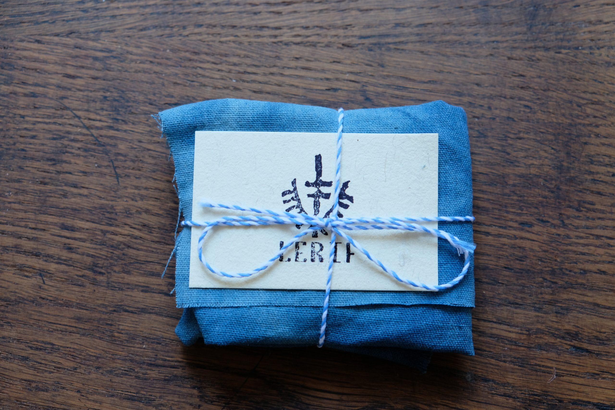 Lerif Designs leather goods packaging wrapped in indigo cloth with blue string and calling card