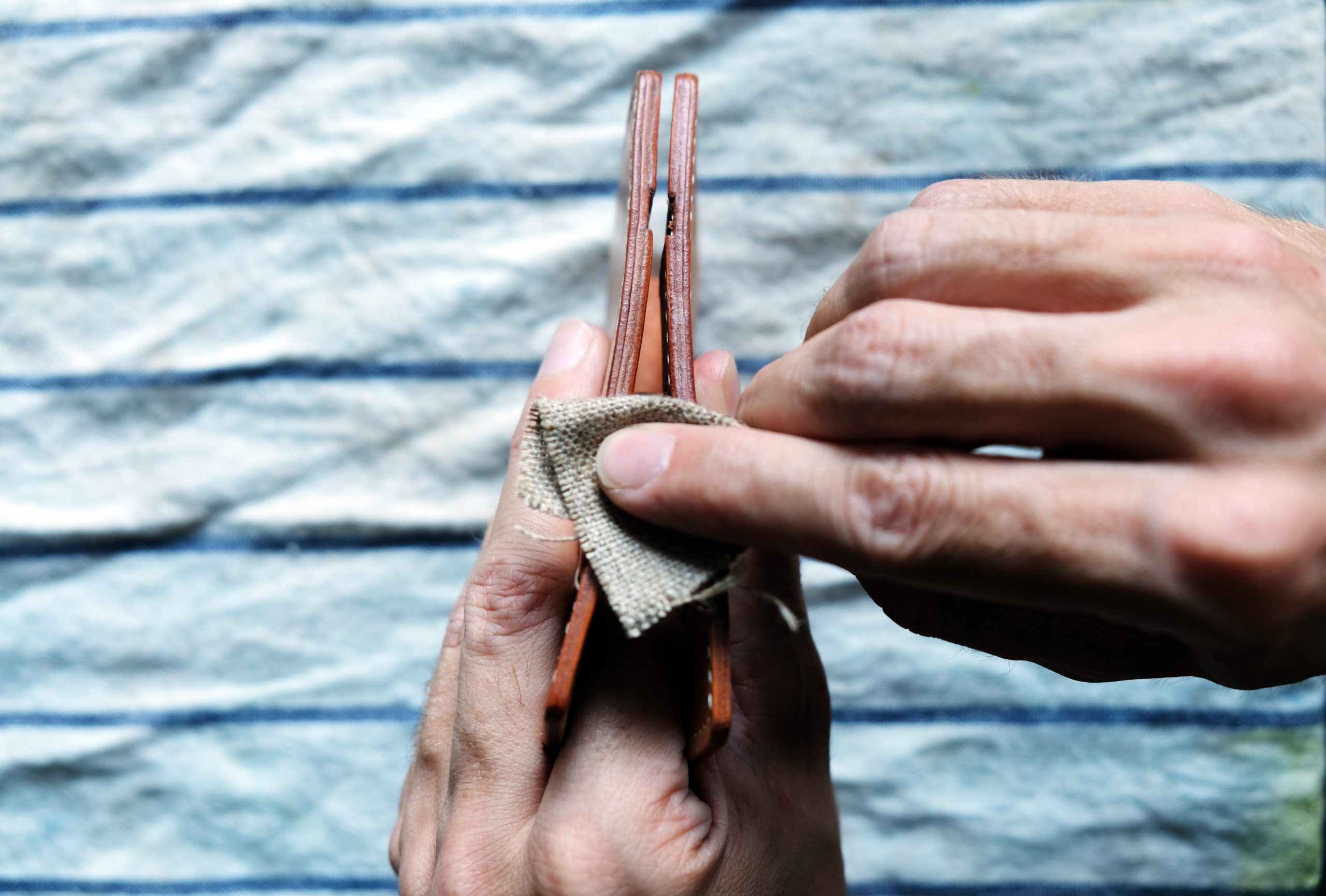 lerif designs leather craftsman polishing edges on a wallet with canvas