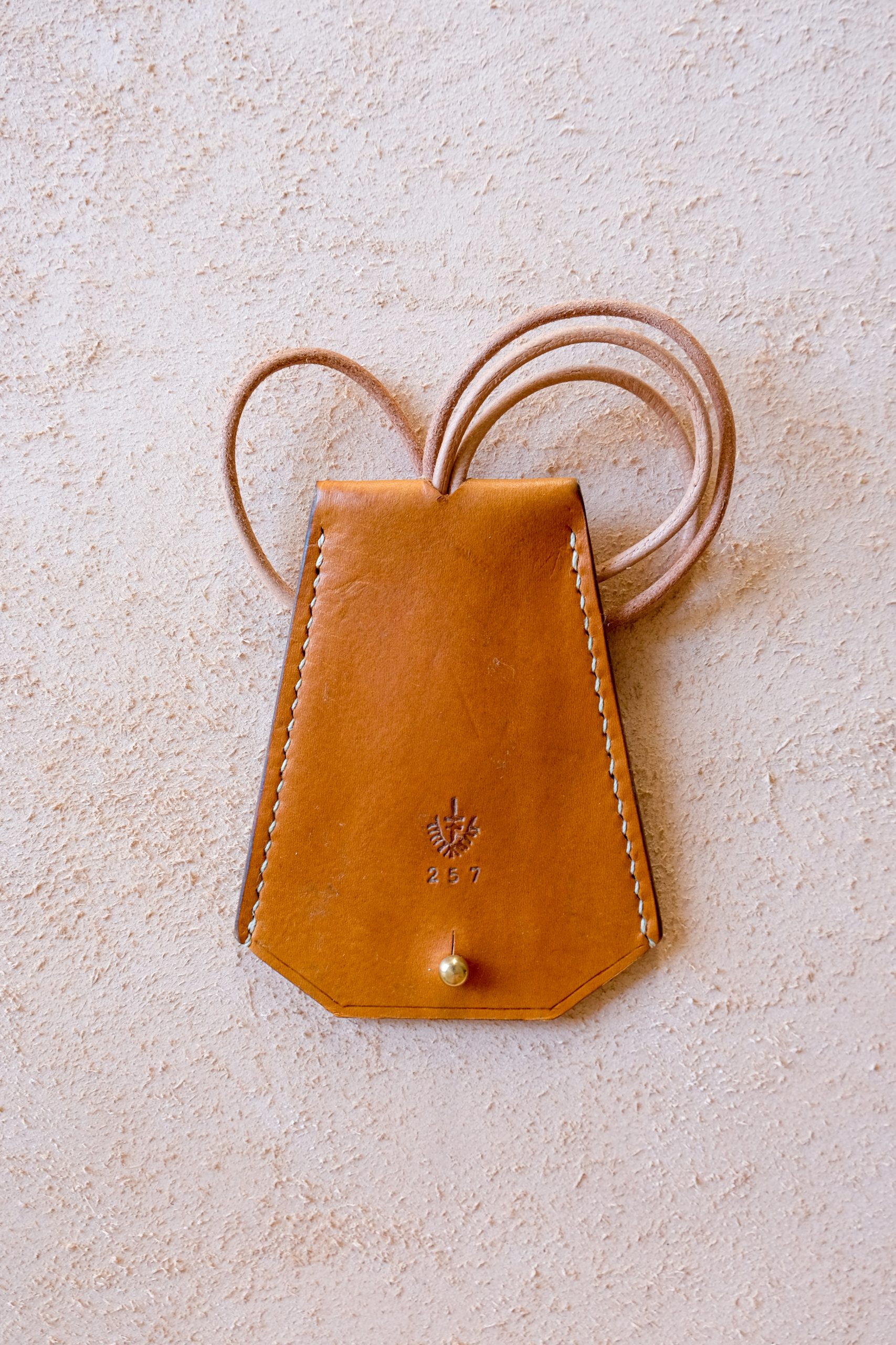 lerif designs leather bell keyholder in turmeric on beige background