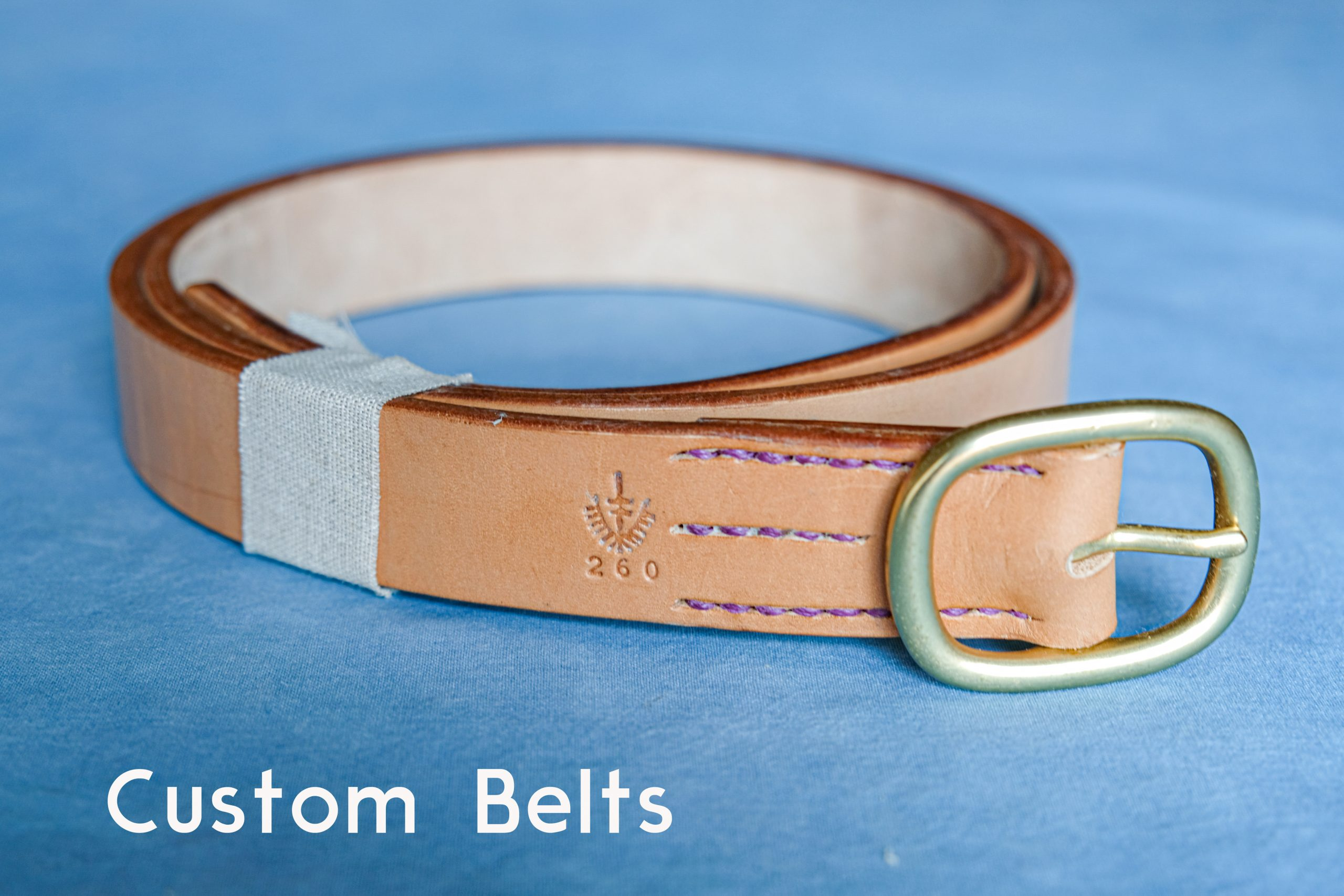 lerif designs custom leather belt with brass buckle on blue background