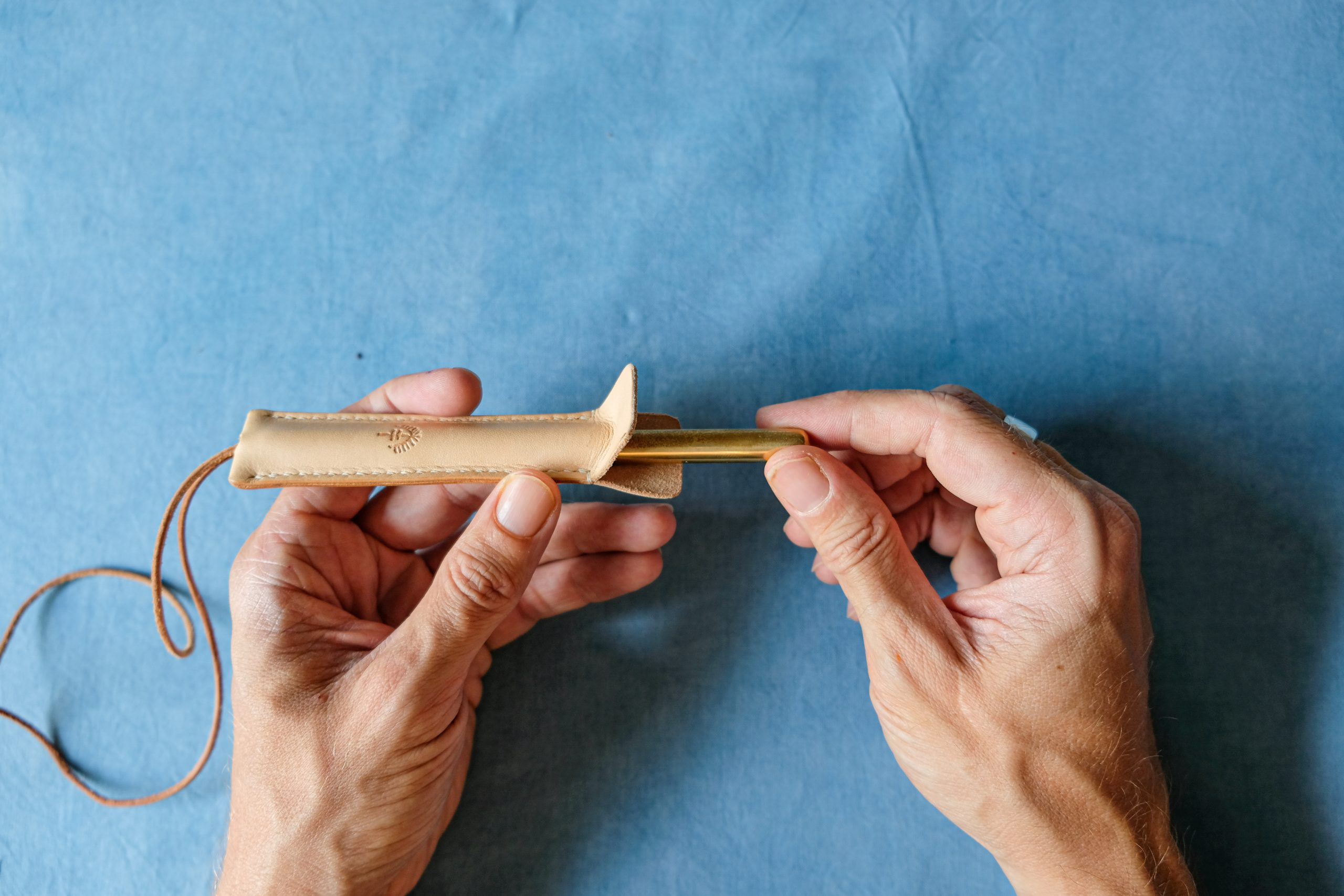 lerif designs leather pen etuis demo pulling out brass pen on indigo background