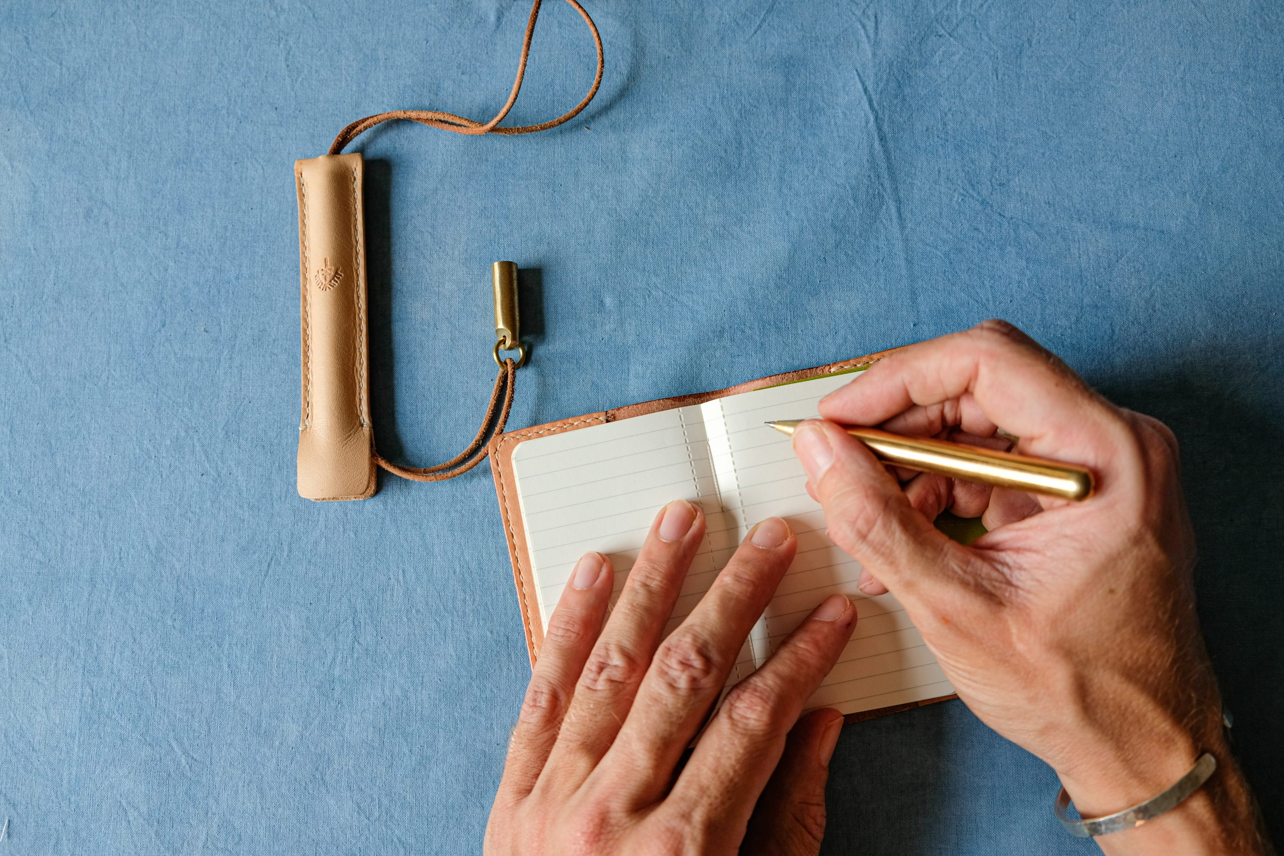 lerif designs leather pen etuis demo writing with brass pen in mini notebookon indigo background