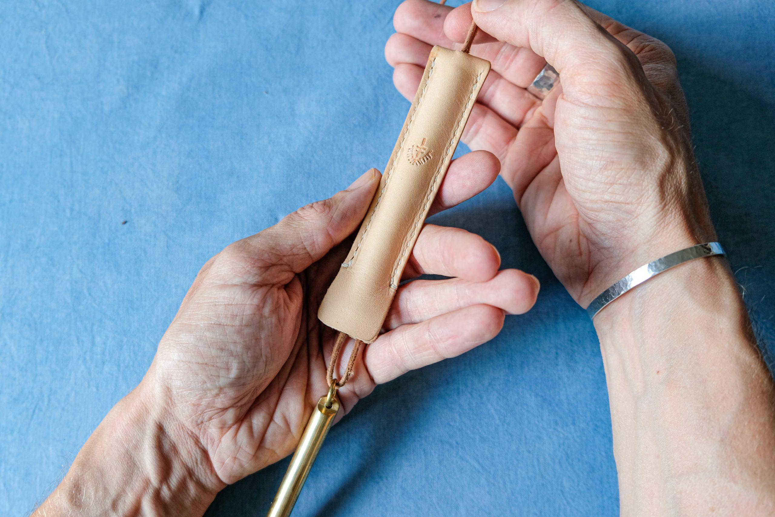 lerif designs leather pen etuis demo pulling in brass pen on indigo background